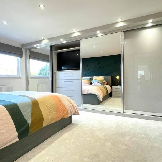 Light Grey & Mirror Sliding Wardrobes With Built in TV Unit by James Kilner in Wakefield
